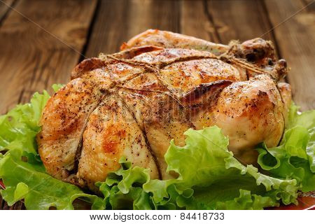 Bondage Shibari Roasted Chicken With Salad Leaves On Red Plate On Wooden Background Closeup