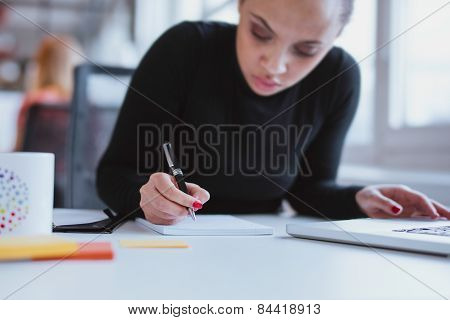Young Woman At Her Desk Taking Note