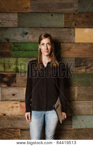 Beautiful Young Businesswoman Standing Against A Wooden Wall