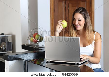 Entrepreneur Woman Browsing A Laptop And Eating At Home