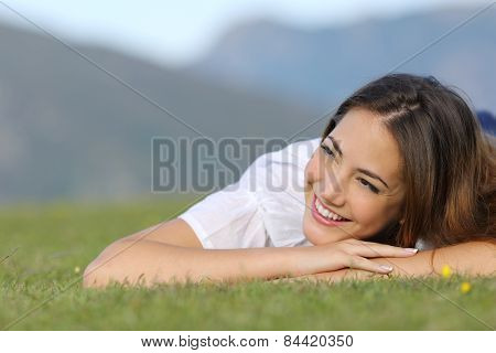 Pretty Happy Woman Thinking On The Grass And Looking At Side