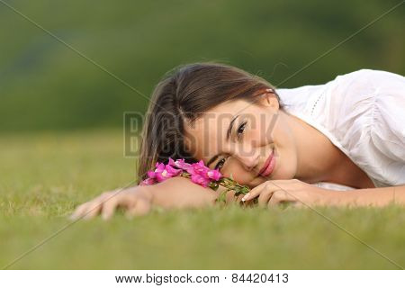 Relaxed Woman Resting On The Green Grass With Flowers
