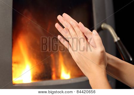 Woman Hands Heating In Front A Fire Place