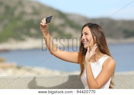 Woman Greeting While Photographing A Selfie With A Smartphone
