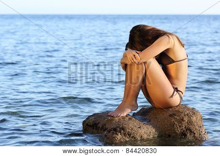Worried Woman Sitting On A Rock On The Beach