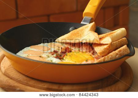 Pan Of Fried Eggs , Bread And Bacon In A Pan On A Table.