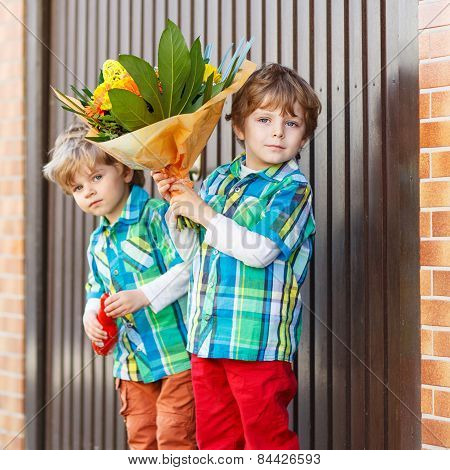 Two Happy Adorable Little Sibling Boys With Blooming  Flowers