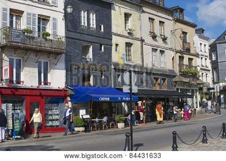 People walk by the street in Honfleur, France.