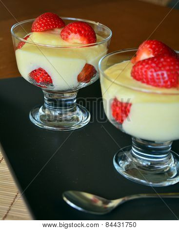 Vanilla pudding with fresh strawberries on the wooden table
