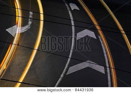 Lines on a road with light trails passing through