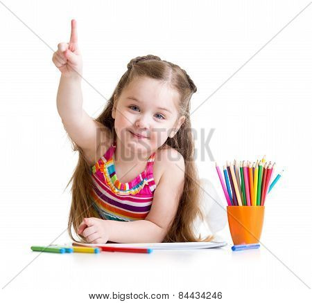 Happy little girl drawing with pencils in preschool