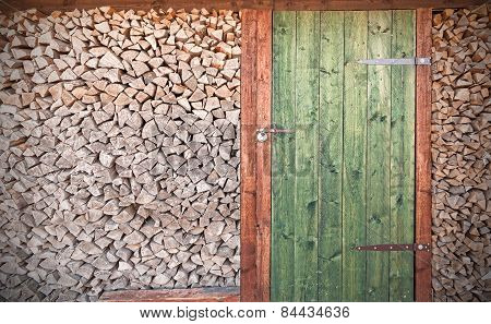 Retro Photo Of Old Rustic Wooden Door With Firewood.