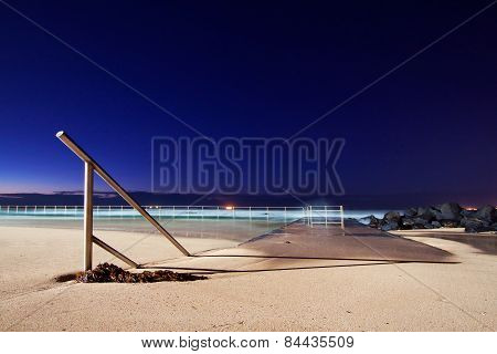 Hand rail going into the sand near a swimming pool