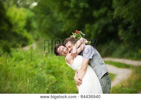 happy bride groom standing in green park