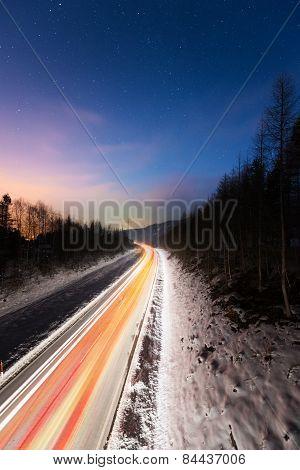 illuminated car lights on street at winter night