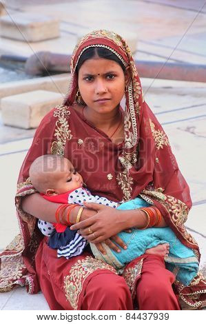 Delhi, India - November 5: Unidentified Woman With Unidentified Baby Sits At Jama Masjid On November