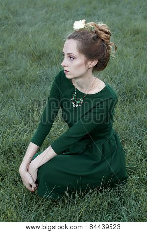 Cheerful Caucasian Woman With Green Eyes And Green Dress Looking Away