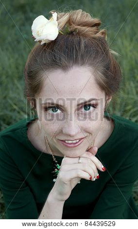 Cheerful Caucasian Woman With Green Eyes And Green Dress Looking At The Camera And Smiling