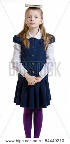 The girl keeps the book on the head in a school uniform
