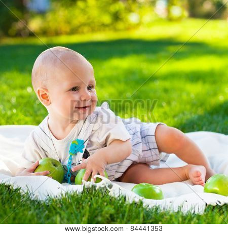 Happy Baby Boy With Green Apples On Green Grass In Summer Park