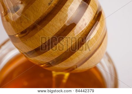 Glass Can Full Of Honey And Wooden Stick In It.