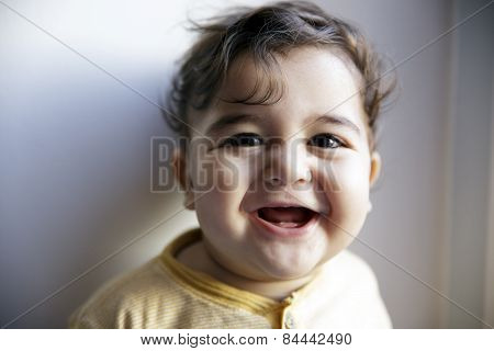 Charming 8 months old baby boy looking cheerful and laugh