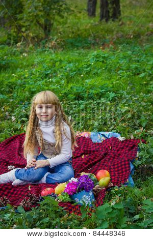 Beautiful little young baby sitting on a red plaid. Lovely child smiling with bright flowers