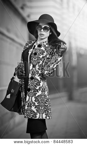 Attractive young woman in a winter fashion shot. Beautiful fashionable young girl in black posing