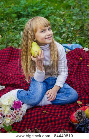 Beautiful little young baby in a pink hat with pear in hand. Beautiful child sitting on a red plaid