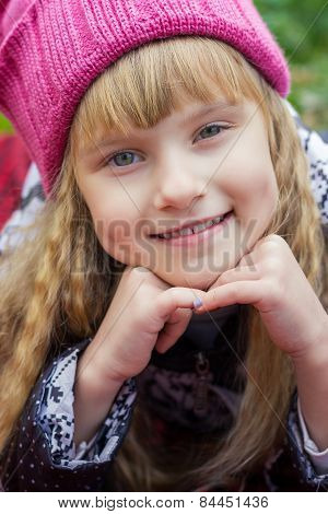 Beautiful little young baby in a pink hat. Beautiful child sitting on a red plaid.
