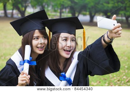 Two Happy Women In Graduation Gowns Taking Picture With Cell Phone