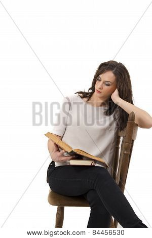 Beautiful Woman Sitting On A Chair And Reading A Book