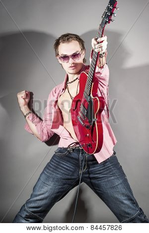 Music Concept: Portrait Of Expressive Caucasian Male Guitarist Playing The Guitar With Passion. Lift