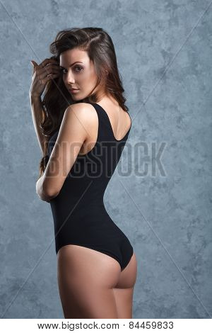 woman in black leotard posing on grey background