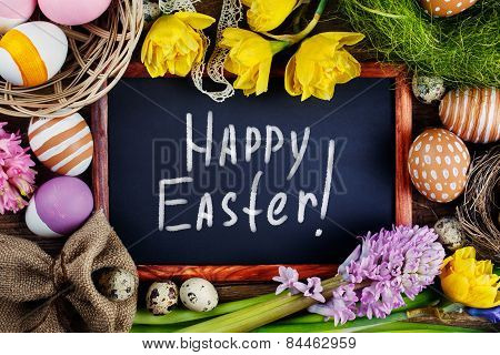 Black Board On Wooden Table With Text - Happy Easter.