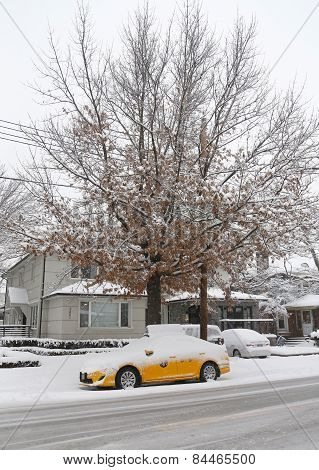New York Yellow taxi under snow in Brooklyn, NY during massive Winter Storm Thor
