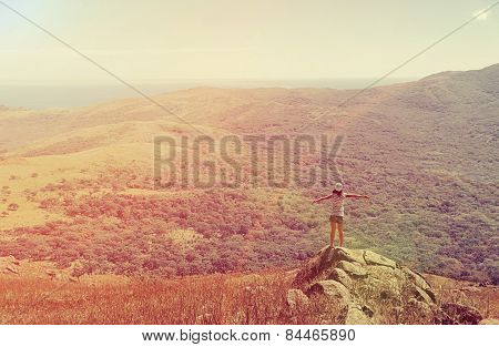 Woman Standing On Peak Of Rock At Sunny Day