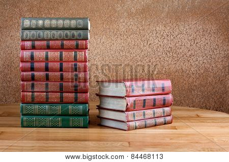 Richly Decorated Volumes Of Books With A Gold Lettering On The Beautiful Wooden Shelf