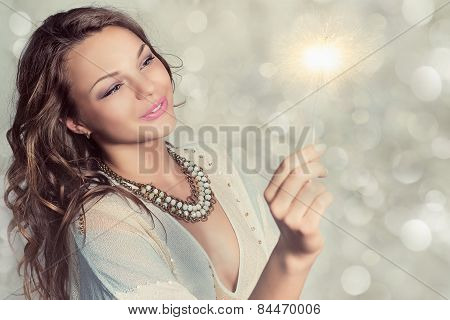 Portrait of a beautiful young woman with a sparkler.