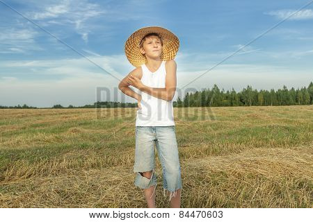 Teenage Farmer Standing On Harvested Field