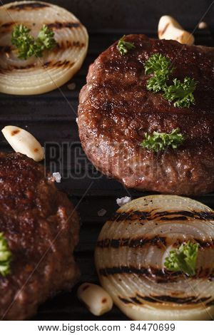 Grilled Burgers With Onions On The Grill Close Up. Vertical