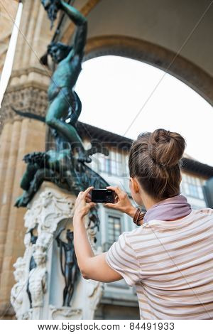 Young Woman Taking Photo Of Statue Perseus With The Head Of Medu