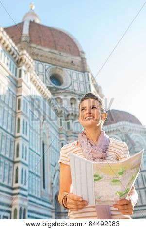 Happy Young Woman With Map In Front Of Cattedrale Di Santa Maria Del Fiore In Florence, Italy Lookin