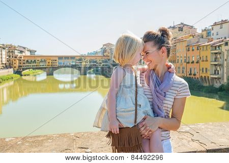 Happy Mother And Baby Girl Hugging On Bridge Overlooking Ponte Vecchio In Florence, Italy