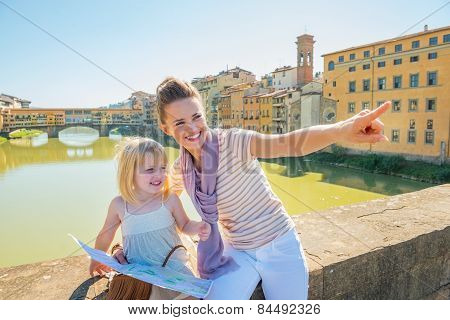 Happy Mother And Baby Girl With Map Sitting On Bridge Overlooking Ponte Vecchio In Florence, Italy A