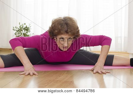Senior Woman Exercising Yoga At Home