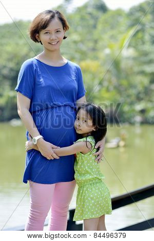 Pregnant Woman Posing In Park With Her Daughter