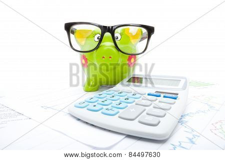 Market Charts With Piggy Bank And Calculator Over It - Studio Shot
