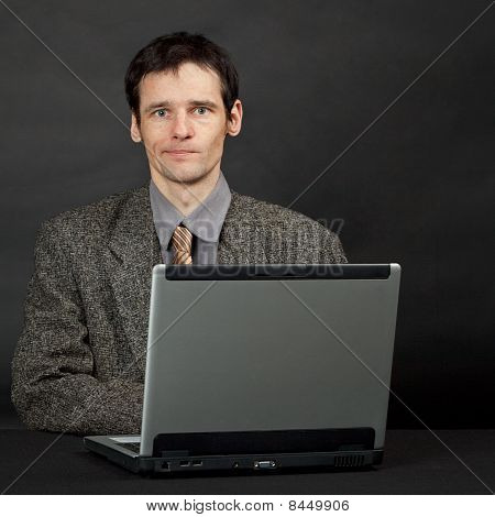 Young Man Sitting At Table With Computer