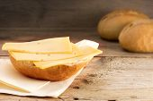 image of bread rolls  - half a bun with cheese and blurry bread rolls in the background on old wood - JPG